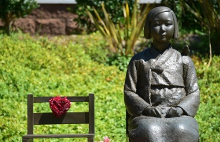 The Comfort Woman statue, with bird on shoulder, beside an empty chair symbolizing survivors who are of an old age without having yet witnessed judgement, in Glendale, California on September 9, 2014, a day after reports that opponents of the statue have appealed the August decision by U.S District Judge Percy Anderson against removing the memorial dedicated to women who were coerced into sexual slavery during World War II by Japan, ruling the 1,100-pound memorial did not cause harm to the plaintiffs nor break any laws. The statue was installed at Glendale's Central Park in July 2013. AFP PHOTO / Frederic J. BROWN (Photo credit should read FREDERIC J. BROWN/AFP/Getty Images)